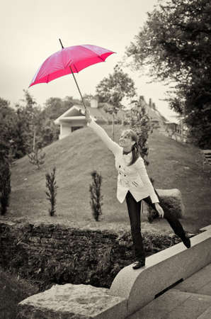 Young woman with umbrella in the park. Black and white photo