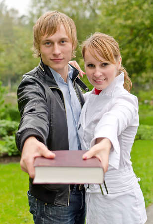 Two students with book in the park photo