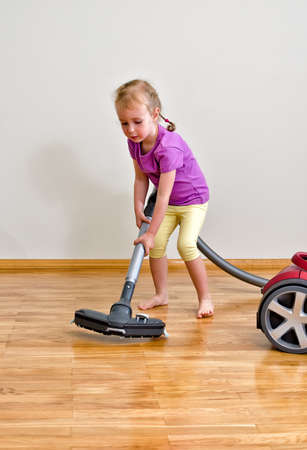 vac: Cute little girl cleaning floor with vacuum cleaner Stock Photo