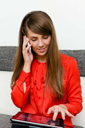 Pretty girl with tablet computer talking on the phone Stock Photo - 15303986