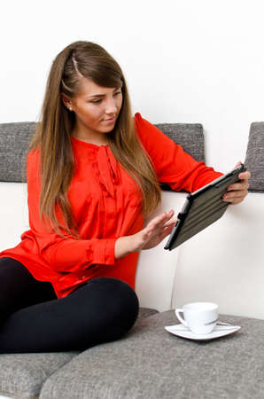 Pretty girl with tablet computer sitting on the sofa photo