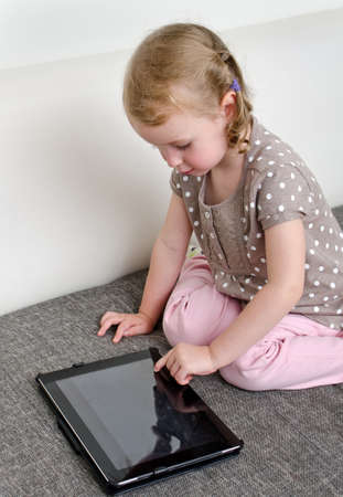 Cute little girl using tablet computer photo