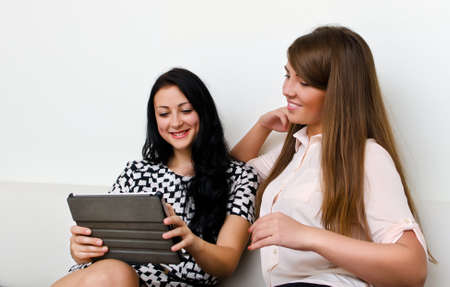Two young women using tablet pc Stock Photo - 15303704