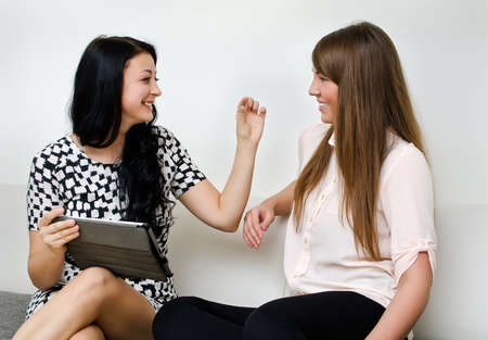 women talking: Two young women chatting sitting on the sofa Stock Photo