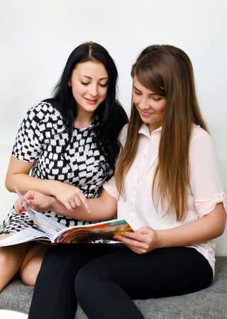 Two pretty girls reading magazine on the sofa photo