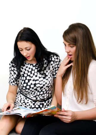 Two pretty girls reading magazine on the sofa Stock Photo - 15303711