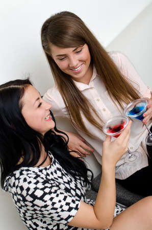 Two female friends drinking cocktail photo