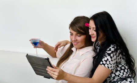 Two young women using tablet pc photo