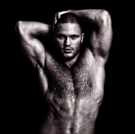uomini nudi: Nudo ragazzo muscoloso in posa con le mani dietro la testa. In bianco e nero
