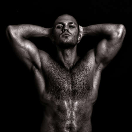 nude sport: Nude muscular guy posing with hands behind head. Black and white Stock Photo