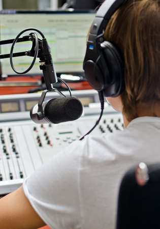 Rear view of male dj working in front of a microphone on the radio photo