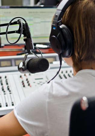 microfono de radio: Vista trasera de un macho dj trabajando delante de un micrófono en la radio