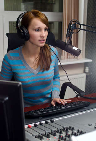 Portrait of female dj working in front of a microphone on the radio photo