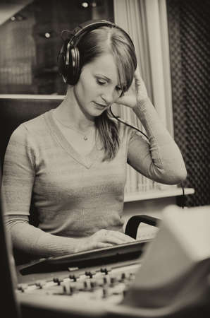 Portrait of female dj working in front of a microphone on the radio. Black and white photo