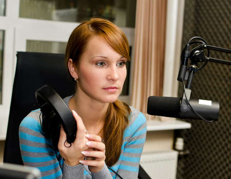 newsreader: Portrait of female dj working in front of a microphone on the radio