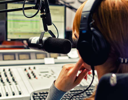 Vista posteriore della femmina dj di lavoro di fronte a un microfono alla radio