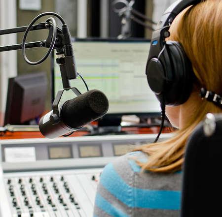 Achteraanzicht van vrouwelijke dj die werkzaam zijn in de voorkant van een microfoon op de radio Stockfoto