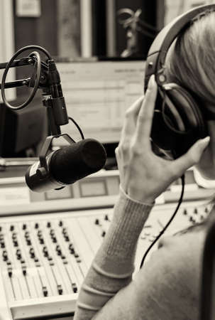 presenting: Rear view of female dj working in front of a microphone on the radio. Black and white