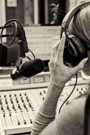 microfono de radio: Vista posterior de la hembra dj trabajando delante de un micrófono en la radio. En blanco y negro