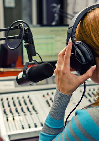 radio dj: Rear view of female dj working in front of a microphone on the radio