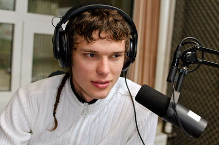 newsreader: Portrait of male dj working in front of a microphone on the radio