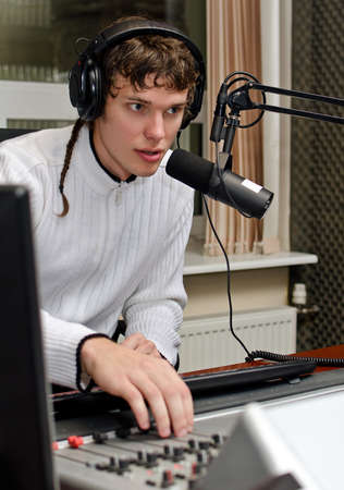 hosts: Portrait of male dj working in front of a microphone on the radio