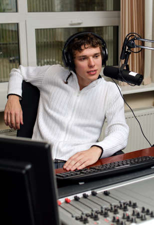 Portrait of male dj working in front of a microphone on the radio photo