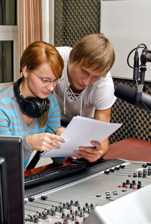 Colleagues examine broadcast list in studio photo