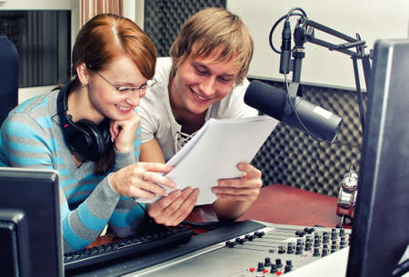 examine: Colleagues examine broadcast list in studio