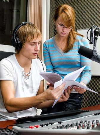 Colleagues examine broadcast list in studio