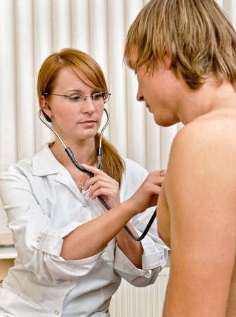 Young female doctor examine male patient with stethoscope Stock Photo - 15689088