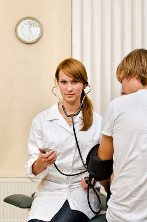 Young female doctor measuring patient's blood pressure Stock Photo - 15689070