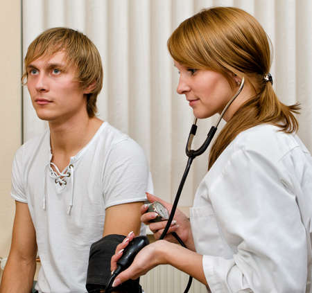 Young female doctor measuring patient's blood pressure Stock Photo - 15689098
