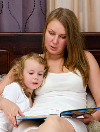 upper half: Young woman and little girl read a book lying in bed