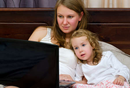 woman lying in bed: Young woman and little girl watching cartoons on laptop lying in bed