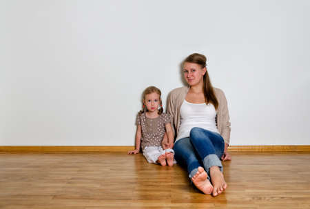 Young woman and little girl sitting on the wooden floor against white wall photo