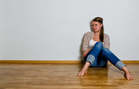 sitting on floor: Young woman sitting on the wooden floor against white wall Stock Photo