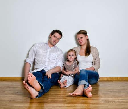 壁に対して床に座って幸せな家族