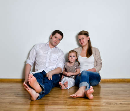little girl barefoot: Happy family sitting on the floor against the wall Stock Photo