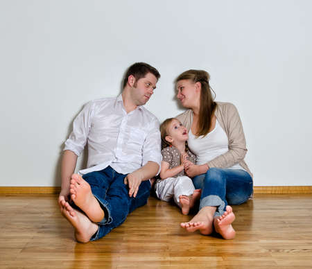 Happy family sitting on the floor against the wall photo