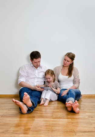 Happy family sitting on the floor against the wall and using tablet computer photo