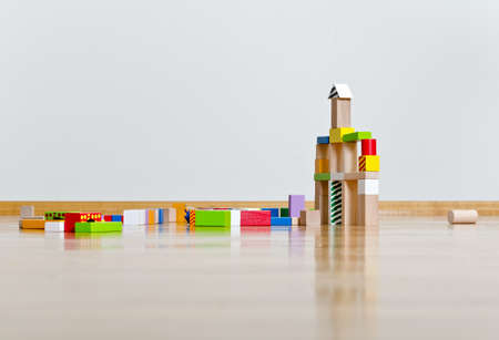 Multicolored building blocks on wooden floor against white wall photo