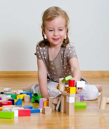 tower block: Cute little girl sitting on the floor and playing with building blocks