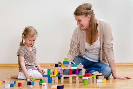 かわいい小さな少女と若い女性は床に座ってとビルディング ブロックで遊んで