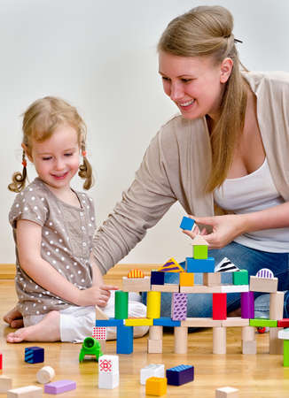 Little girl and young woman having fun playing with building blocks on the floor photo