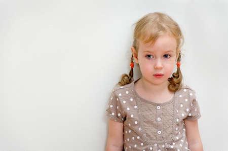 ojos tristes: Retrato de ni�a triste de pie contra la pared del espacio para el texto Foto de archivo