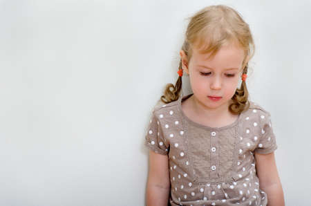 Portrait of sad little girl standing against the wall  Space for text photo
