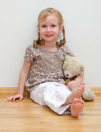 Cute little girl sitting with teddy bear on the floor against the wall photo