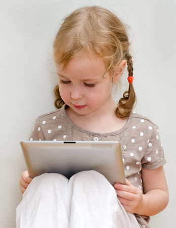 eyes looking down: Cute little girl sitting against the wall and using tablet computer