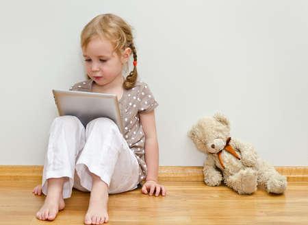 bionda occhi azzurri: Carino bambina seduta sul pavimento contro il muro e utilizzando il computer tablet